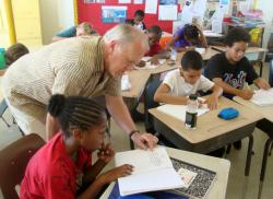 Author Steve Swinburne looks over Rex Cazaubon's opening paragraph while his classmates are lost in their writing.