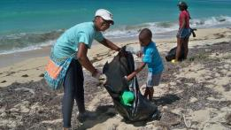 Jether William, left, and her five-year-old son, Gabriel, pick up trash at Sandy Point Refuge.
