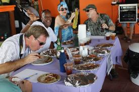 Judges sample ribs from a dozen contestants.