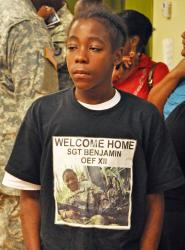 "Joseph Harris, 15, waits to greet his sister, V.I. Guardswoman Asheba Benjamin. Seven members of Benjamin's welcoming party wore T-shirts the same as this one. The back read, ""At Ease."""