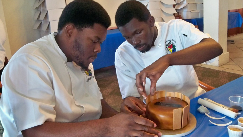 Local culinary students Romano Thomas, left, and Deshaun Quinland decorate a cake.