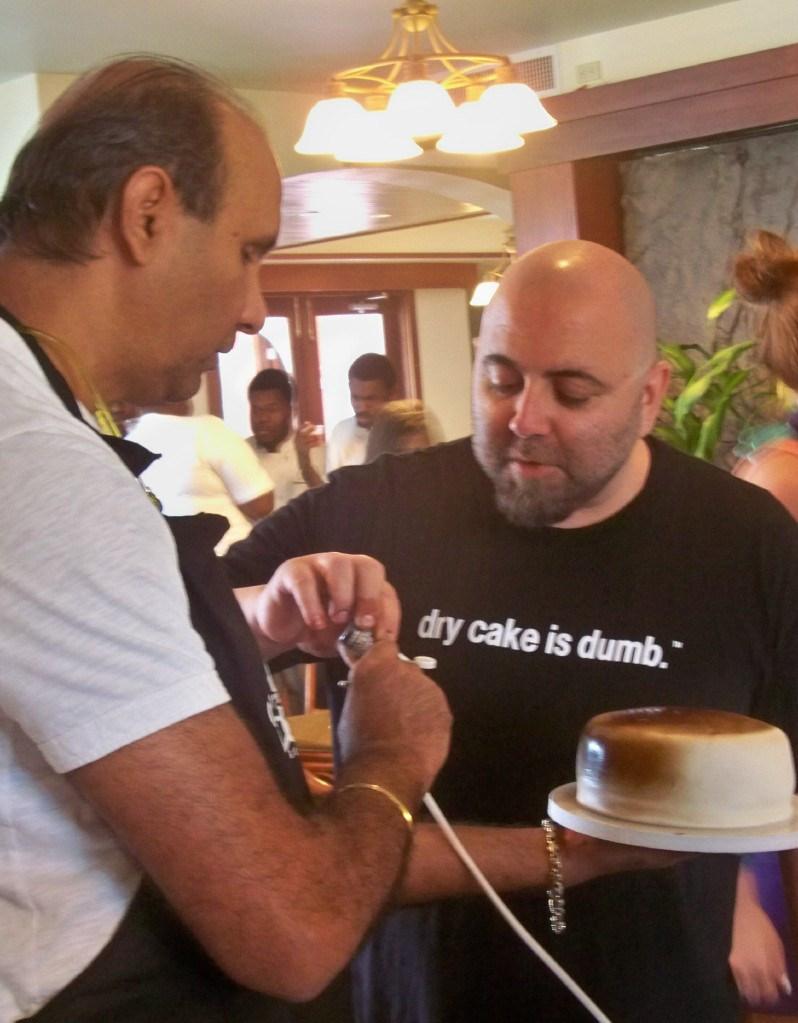 Gary Udhwani, left, and Chef Duff airbrush a cake.