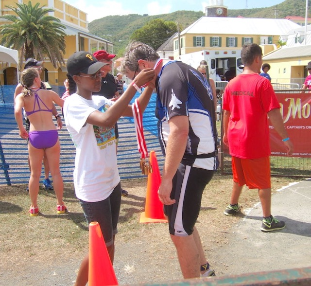 A competitor receives a medal after finishing the grueling triathlon.