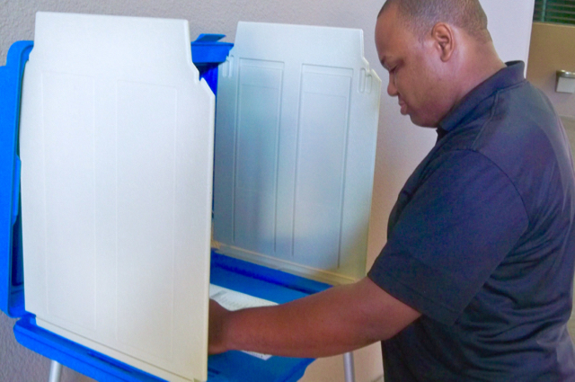 Terrell Alexandre demonstrates how the ballots and voting machines work.