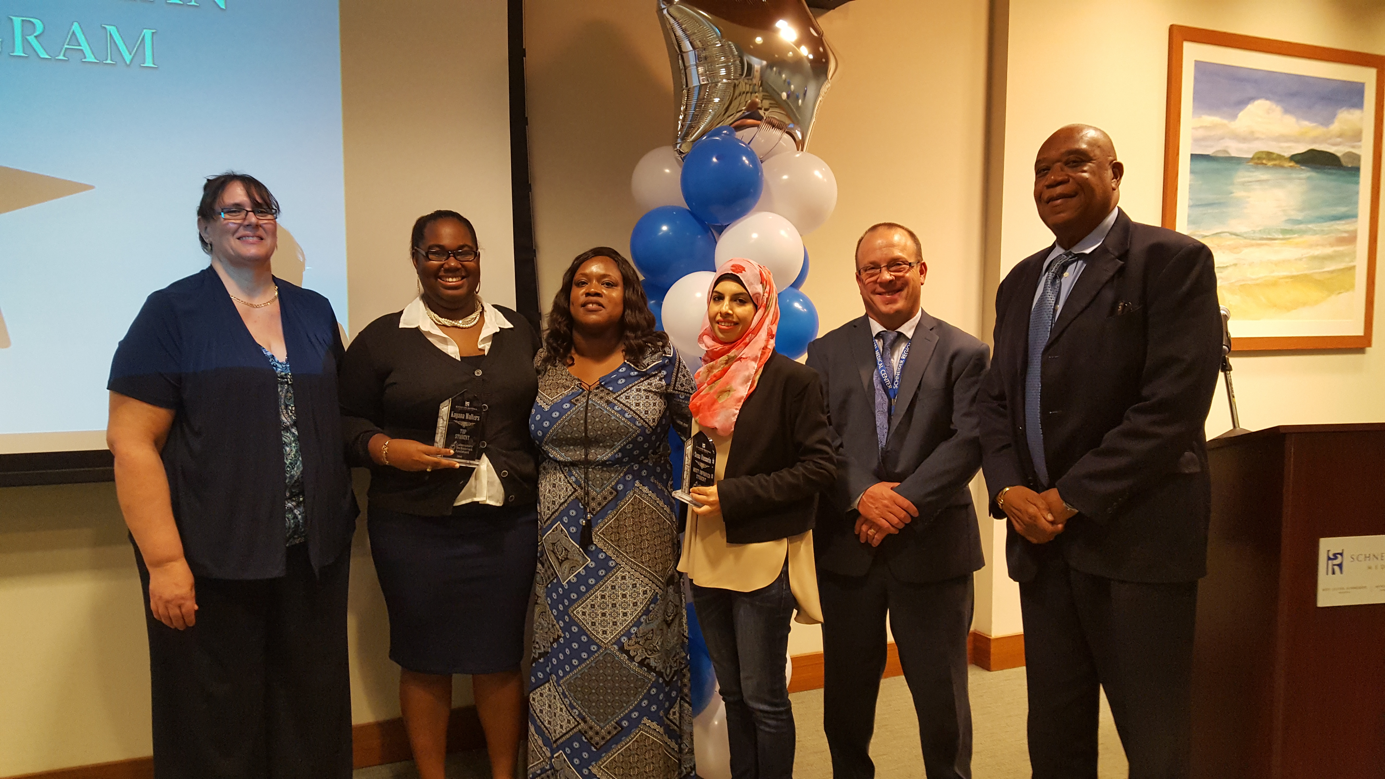 (left to right) Carol Kelly, lead medical technologist at SRMC; Kayana Walters, graduate and valedictorian of class; Mauritza Phillip, clinical laboratory director; Sena Hussein, graduate; Charles Nickerson, SRMC VP of Operations; Bernard Wheatley, SRMC CEO; (not pictured - graduate Amira Plaskett)