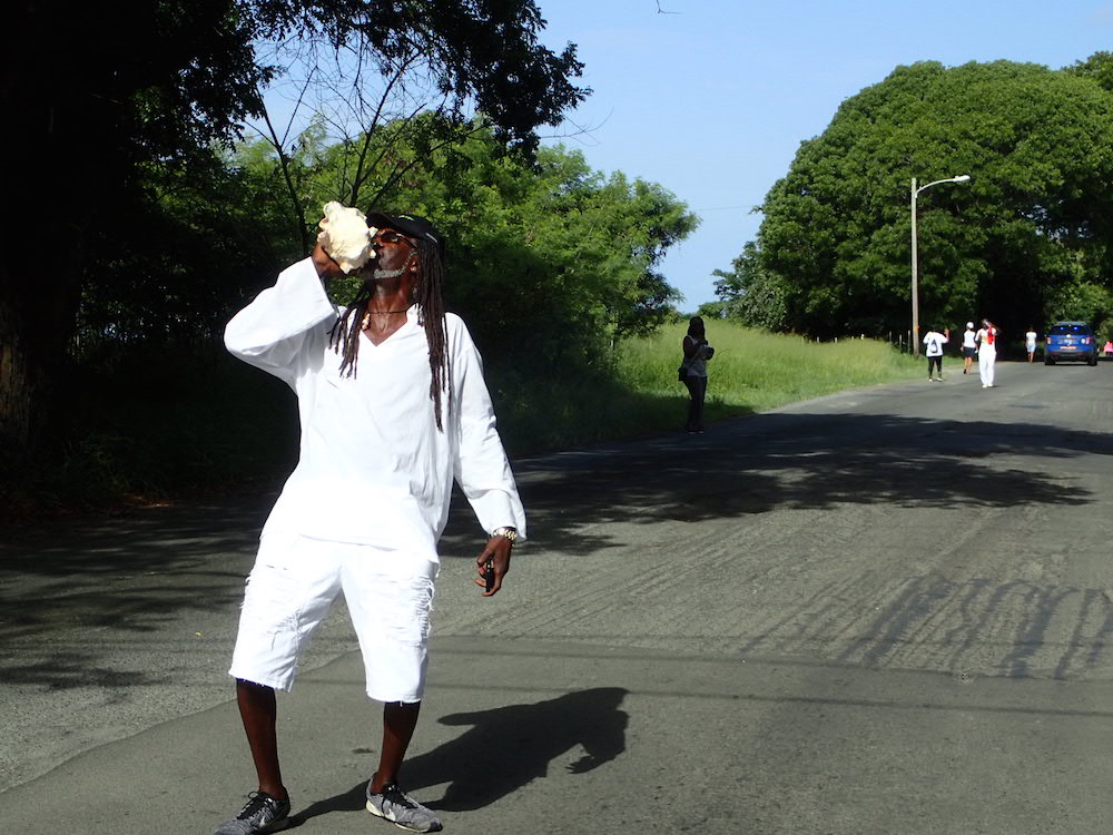 """Several hundred march along Queen Mary Highway from Christiansted to Frederiksted in 17th annual Emancipation March Monday, organized by Sen. Terrance """"Positive"""" Nelson (blowing the conch shell)."""