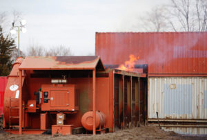 "An air curtain incinerator in use at Floyd Bennet Field, Brooklyn, New York, after Hurricane Sandy. (Image from ""Notice of Intent to File Suit"" from the Environmental and Natural Resources Law Clinic at Vermont Law School.)"