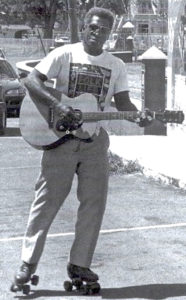 McIntosh plays guitar while roller skating in 1999 photo. (From McIntosh family)