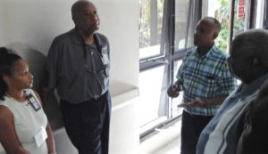 Health and hospital officials talk in a dimly lit corridor of the Myrah Keating Smith Clinic about the future of health care on St. John, with Gov. Kenneth Mapp, right. Also pictured, from left, Dr. Tai Hunte, Dr. Bernard Wheatley, and Darryl Smalls.