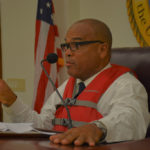 Sen. Brian Smith (D-STT) wears a life vest while chairing Friday's Homeland Security, Justice and Public Safety Committee hearing, in a gibe at VITEMA's late tsunami alert. (Photo by Barry Leerdam, provided by the V.I. Legislature)