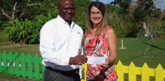 Luis Sylvester presents a donation to Dana Holtz, director at Queen Louise Home in Frederiksted.
