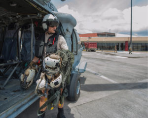 Naval Aircrewman 2nd Class Nicholas Glass carries flight gear back to an MH-60S Sea Hawk helicopter during humanitarian relief efforts in the wake of Hurricane Irma in September 2017. (U.S. Navy picture by Mass Communication Specialist 3rd Class Sean Galbreath/Released)