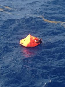 A Coast Guard rescue swimmer grabs hold of a life raft Thursday about 32 miles south of St. Croix. The helicopter crew rescued two people who had abandoned their sinking vessel. (Coast Guard photo)