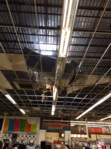 One of 18 air conditioning units that fell through the roof after Hurricane Irma dangles from the ceiling of the Tutu Park Kmart. (Photo by Brendda Burrows)