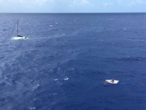 Robert Petersen of St. Thomas sits in his life raft as a Coast Guard rescue swimmer talks to him Friday, with the sunken 36-foot sailing vessel Wings in the background, about six miles southwest of Big Sand Cay in the Turks and Caicos. (U.S. Coast Guard photo)