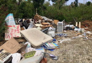 This bin site near Great Cruz Bay has become a dumping ground for all kinds of debris that does not belong there. An overturned sign reads, 'Stop dumping on the ground.'