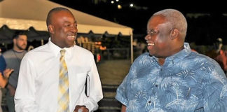"""Gov. Kenneth Mapp and Lt. Gov. Osbert Potter smile and laugh in the official Government House photo from a government sponsored forum in Estate Tutu. The taxpayer-funded Government House statement is headlined """"Recovery Successes Cited by Governor at Packed Town Hall Meeting."""""""