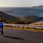 A cyclist rides the road down from Point Udall, with Buck Island in the background. (File photo)