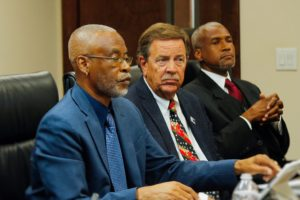 From left, EDC Board Chairman Jose Penn, Vice Chairman Philip Payne and EDA CEO Kamal Latham listen to testifiers during Tuesday's show of cause hearing.