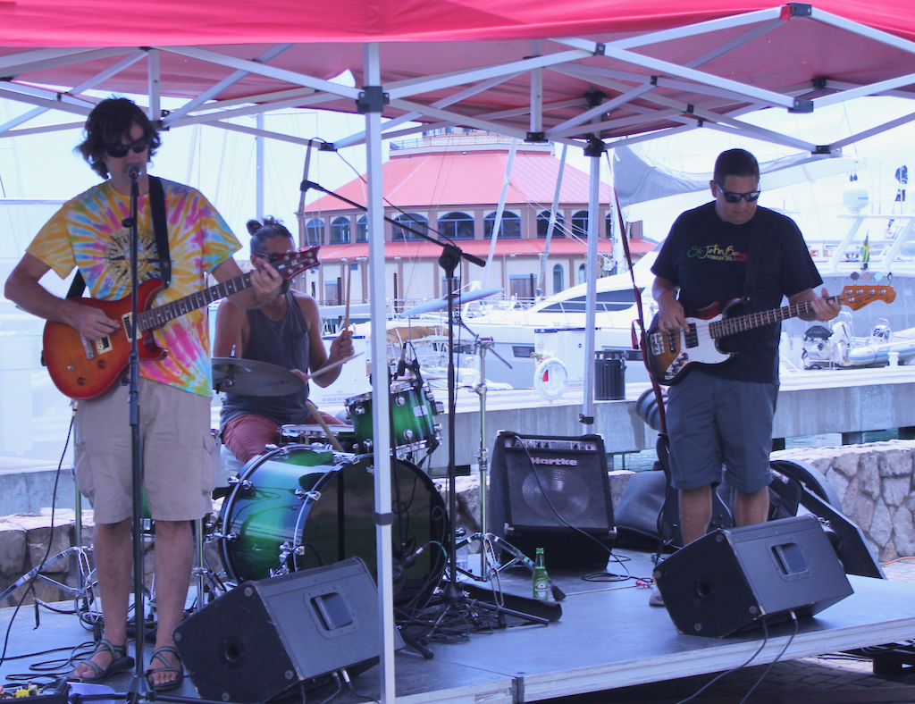 The band Cat 3, consisting of a drummer, bass guitar and singer/lead guitar, entertained festival goers with music from a central stage in Yacht Haven Grande.