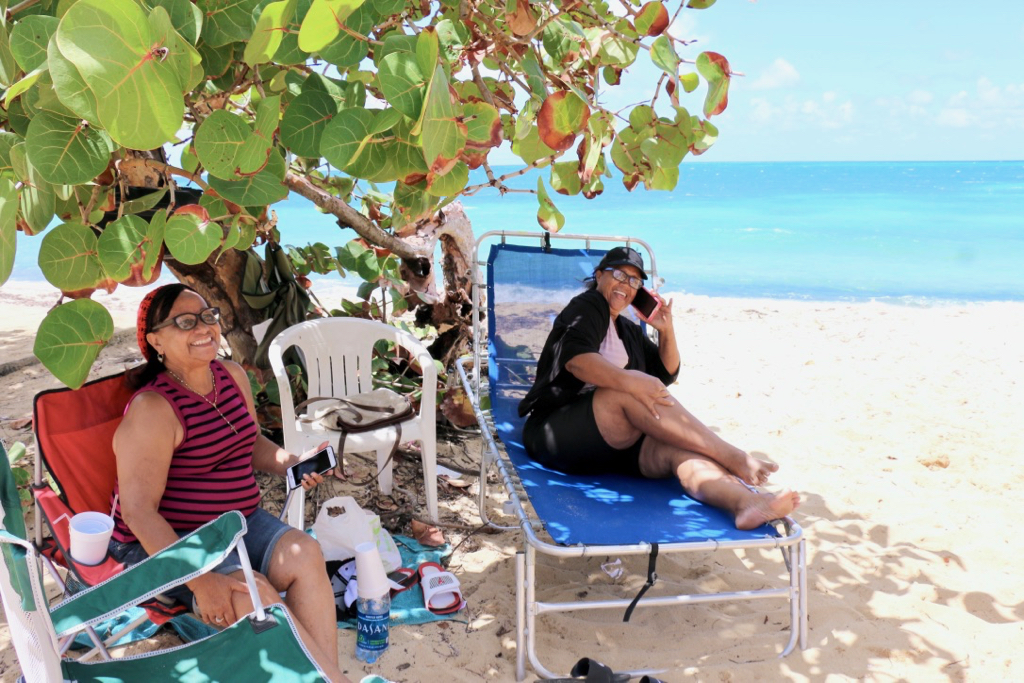 On the beach at Little Bay, Rudidenia Reye and Francia Espinal relax as they wait for family and friends to join them for the afternoon. (Linda Morland photo)