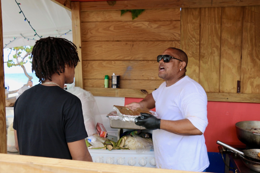 Israel Contreras, busy in the cook tent, gives instructions to one of the campers to pick up any trash on the beach. Passionate about keeping Little Bay clean, Contreras said the campers clean up morning and evening. (Linda Morland photo)