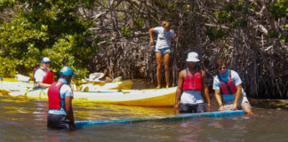 CUTLINE: Volunteers puzzle over how to transport a large piece of plastic docking to shore during Saturday's cleanup. (April Knight photo)