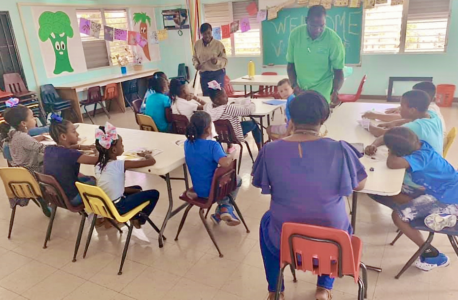 Field technician Ellisha Williams, Principal Rosemond Lawrence-Creighton and teacher Petra Wilson work with St. Croix with students at S. Croix Christian Academy. (Photo by V.I. Next Generation Network)