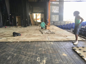 Workmen apply new plywood flooring on top of the old wooden floor. (Eliza McKay photo)