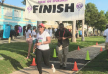 First lady Yolanda Bryan crosses the finish line, followed closely by her bodyguard. (Elisa McKay photo)