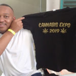 Clayton Thomas displays one of his T-shirts for sale. (Source photo by Susan Ellis)