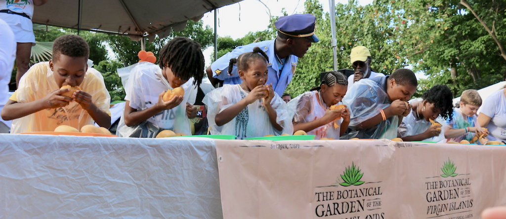 The contestants in the children's mango eating contest were under the watchful eye of the police to be certain everything was on the up and up. (Source photo by Linda Morland)