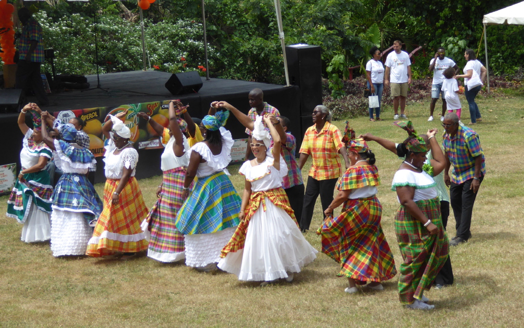 We Deh Yah Cultural Dancers whirl beneath a blazing sun. (Source photo by Linda Morland)