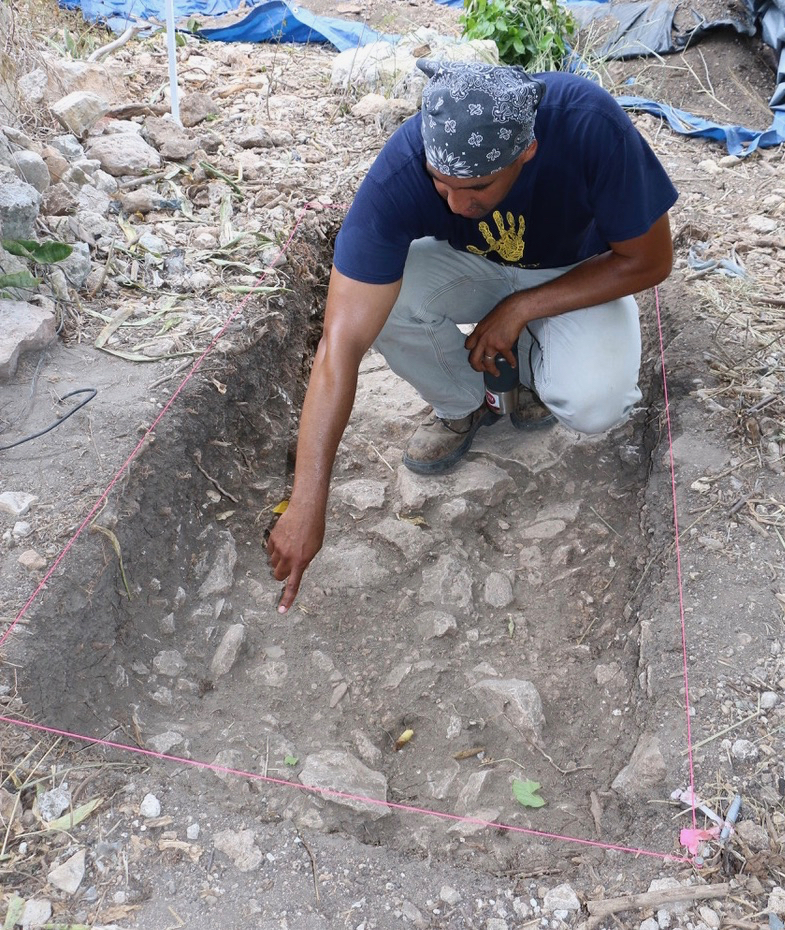 William White of University of California, Berkley, points to clam shells in the pit. He is standing on what the archeologists believe may be a floor. (Source photo by Linda Morland)