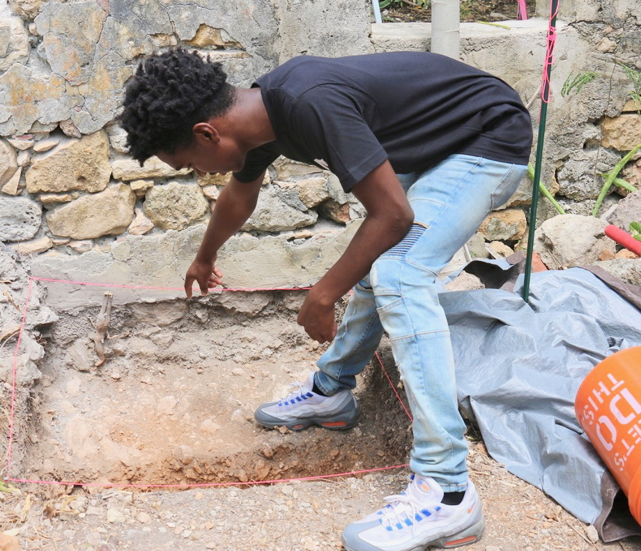 Intern Armani Doward shows the bottom of the cabin wall. Coral blocks make up much of the building materials in the walls. These cabins were in use from the mid 1700s until the 1960s, giving a great opportunity to explore the living conditions over time. (Source photo by Linda Morland)