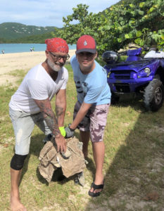 The father and son team of Alexey and Mikhail Dubovoy haul a big chunk of construction waste off Brewers Bay. (Source photo by Teddi Davis)
