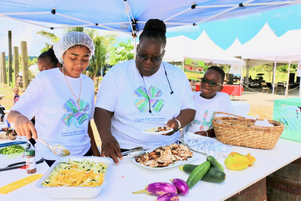 The 4-H Superlicious Chefs dish up sautéed fresh vegetables and marinated chicken cooked over a coal pot. From left: Justic Veira, Dawn Thomas, and Joey Swanson. (Source photo by Linda Morland)