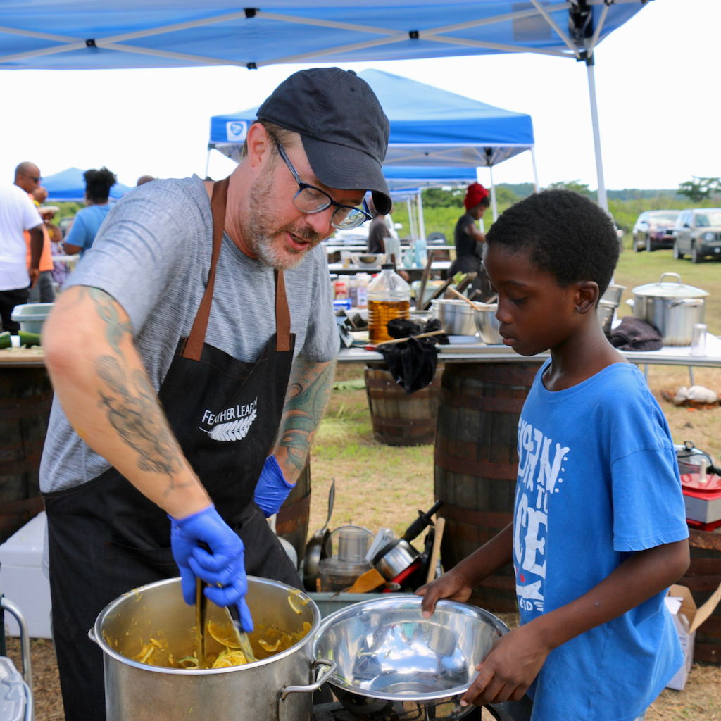 Sugar Apple chef Blake Gardner stirs a pot as Micah Paul, aged 8 assists. Micah says he has already decided to become a chef. (Source photo by Linda Morland)