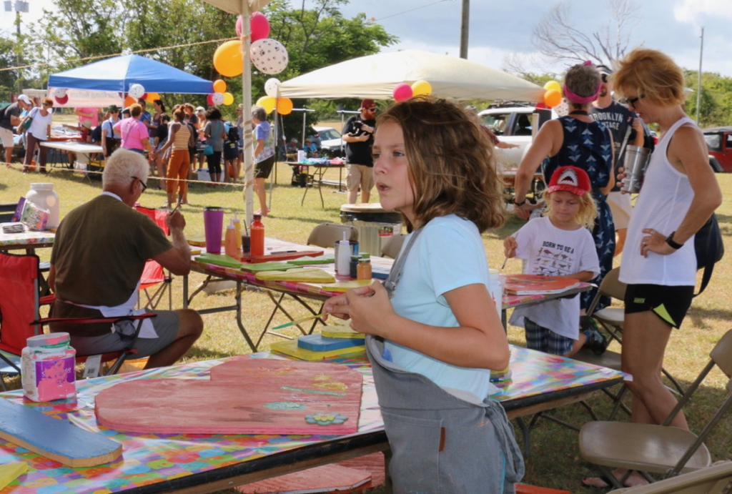 Painting fall decorations, Maeve McKinnon is serious about her work. Many of the fall themed art works were sold and the funds donated by their creators to SCAWC. (Source photo by Linda Morland)