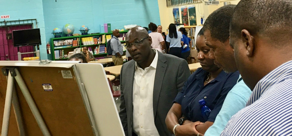 Sens. Novelle Francis, Kenneth Gittens and Kurt Vialet look over displays at Tuesday's Department of Education community meeting. (Source photo by Susan Ellis)
