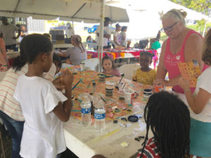 Cindy Salomone shows children how to make bee floats. (Source photo by Susan Ellis)