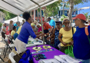 Charmaine Mayer hands out health information to St. John residents.