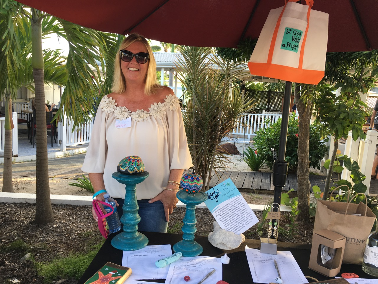 Artist Becky Snodgrass looks over silent auction items Saturday. (Source photo by Susan Ellis)