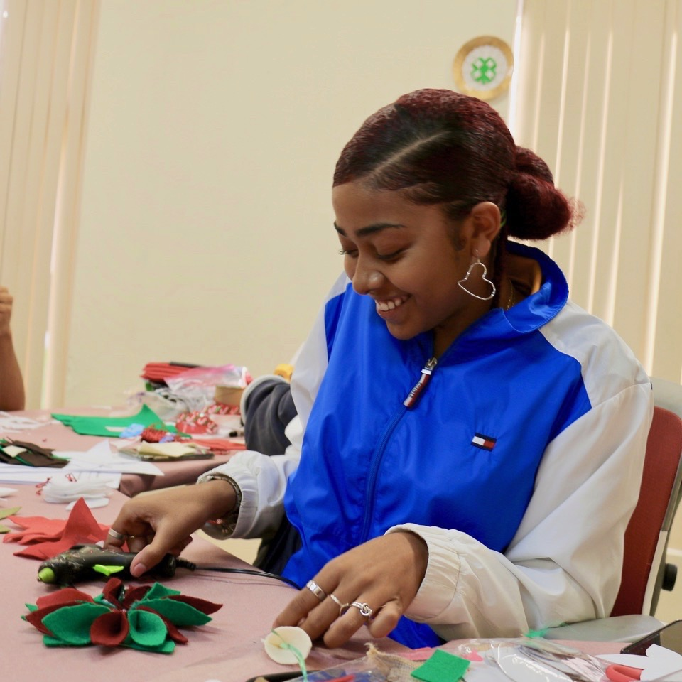 4-H Ambassador, Justice Veira, one of 15 Ambassadors assisting at the event, enjoys the opportunity to help younger children prepare for Christmas. (Source photo by Linda Morland)