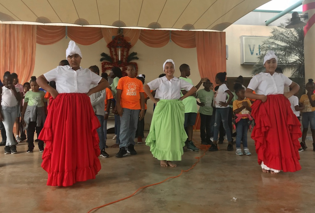 Students dance the Bomba, led by three costumed dancers, Friday at Sunny Isle Shopping Center. (Source photo by Elisa McKay)
