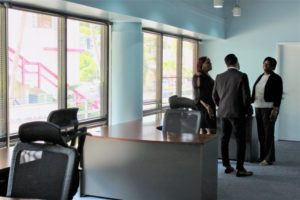 Attendees at the MASA Assist ribbon cutting ceremony chat in the corner of the new office space. (Source photo by Bethaney Lee)