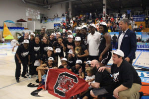Gov. Albert Bryan, in the white shirt, poses with Aliyah Boston and the University of South Carolina women's team as they receive the Reef Division Trophy. (Photo by Basketball Travelers)