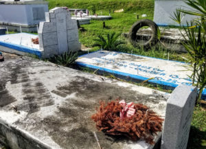 A discarded tire leans against a grave plot in St. Thomas' Western Cemetery. (Source photo by Bethaney Lee)