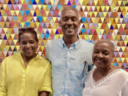 Avelino Samuel, center, and Karen Samuel, right, pose with their sister Coreen in front of a quilt made by Karen. (Photo submitted by the Samuel family)