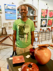 Avelino stands behind some of his carved bowls. (Source photo by Amy Roberts)